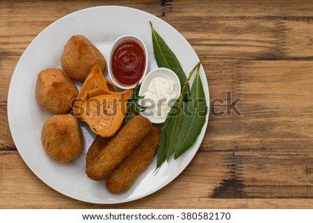 portuguese appetizers with sauces on white plate on brown background - stock photo