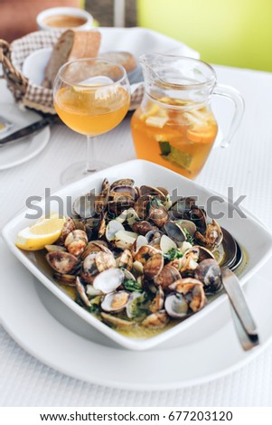 Portuguese Clams in garlic sauce (Ameijoas a Bulhao Pato) with onions  accompanied by white sangria served in Setubal, Portugal.