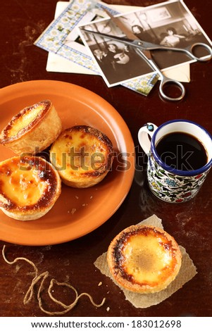 Portuguese Custard Tarts and a cup of coffee, on a dark background. - stock photo
