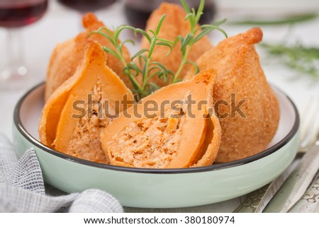 portuguese dish coxinhas de frango on plate with red wine - stock photo