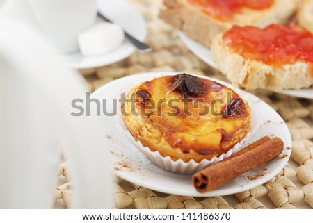 "Portuguese (Europe) traditional Cake ""pastel de nata"" - cream cake on a table with milk coffee and jam toast"
