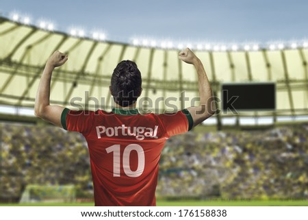 Portuguese soccer player celebrates with the fans on the stadium - stock photo