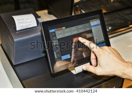 POS terminal in coffee cafe waiter's hand when serving customers and touching screen of a tablet with software interface to take order and print receipt.