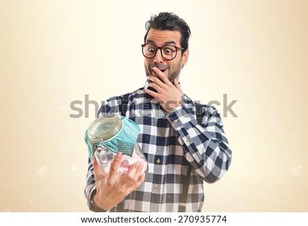 Posh boy  holding glass jar with sweets inside  - stock photo