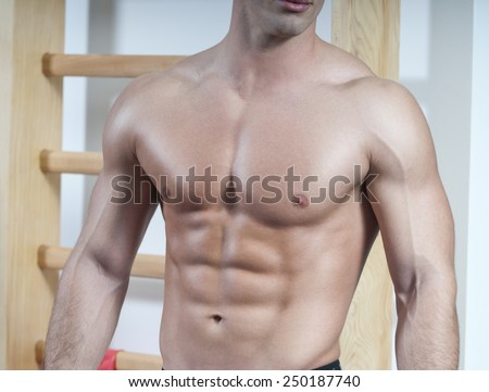 Posing at gym, showing abdominal muscles.