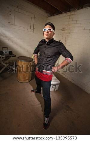 Posing Caucasian rapper in basement with hands on hips - stock photo