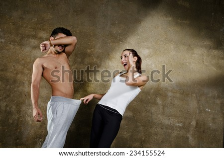 Posing couple in wall background joking about penis and other sexual issues