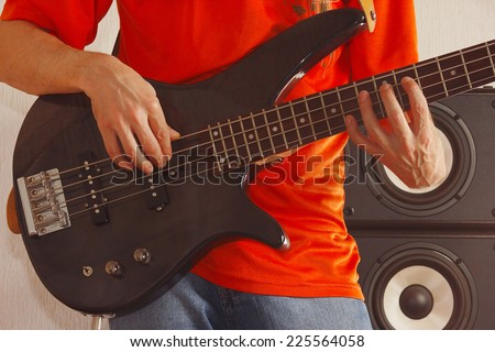 Posing hands of the rock musician playing the bass guitar - stock photo