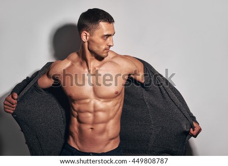posing muscular man about wall