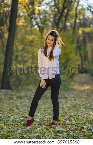 Posing on footpath in forest. A smiling good looking girls is posing in a pink shirt, dark blue jeans and red shoes in an autumn forest while standing on foliage.