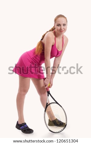 Posing young woman in pink with tennis racket in her hand, on white background