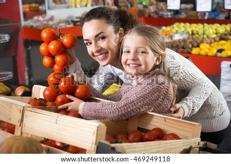 posinive mother and daughter buying tomatoes in shop