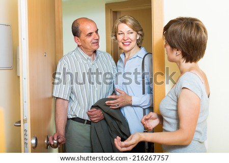 Positive adult  daughter greeting smiling elderly parents at threshold