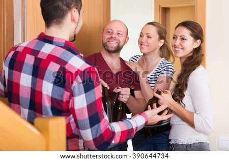 Positive adult friends gathering together at house booze party - stock photo