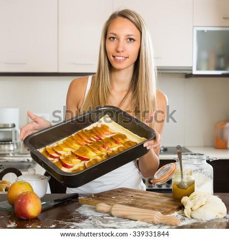 Positive adult girl preparing apple cake in domestic kitchen - stock photo