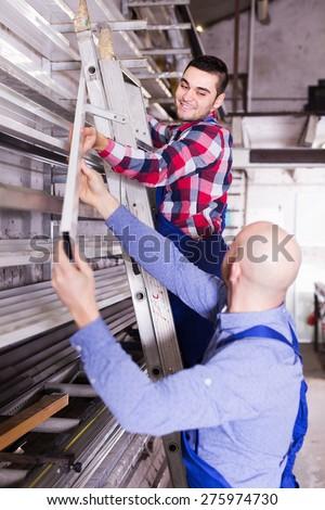 Positive adult workmen choosing PVC window profile at factory - stock photo