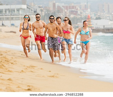 Positive adults running at a sandy beach in a summer day