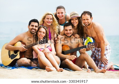 Positive adults with guitar relaxing at a sandy beach in the summer day