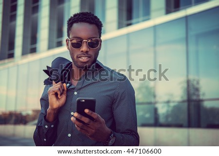 Positive african american male using smartphone outdoor.