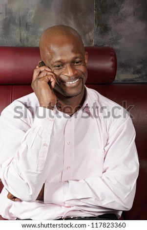 Positive african man in pink shirt talking on mobile phone - stock photo