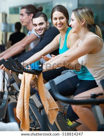 positive american adults riding stationary bicycles in fitness club