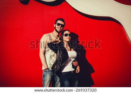 positive and a young couple standing against a bright wall in the city - stock photo