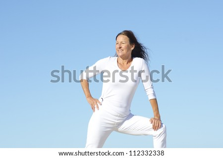 Positive and happy active retired mature woman in white stretching exercises,  isolated with blue sky as background and copy space.