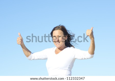 Positive and happy active retired mature woman posing with thumbs up and smile, isolated with blue sky as background and copy space.