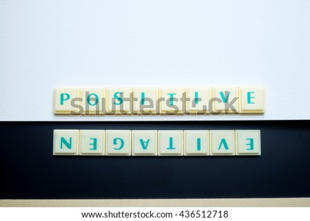 Positive and Negative concept. The words spelled by letters with drawing book on blackboard with wooden border. Space for texts. Dark tone. - stock photo