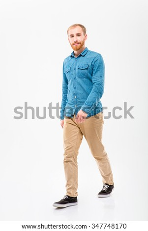 Positive attractive young male with beard walking and looking camera over white background - stock photo