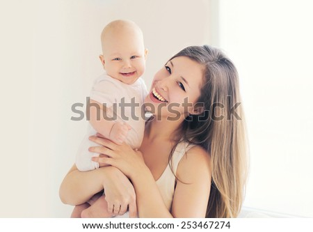 Positive baby and mother at home in light room, soft colors - stock photo