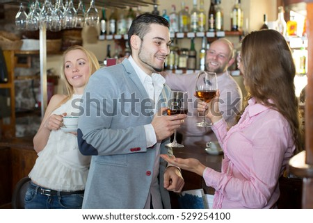 Positive bartender entertaining guests at a bar counter in bar