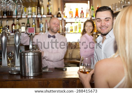 Positive bartender entertaining guests at bar counter
