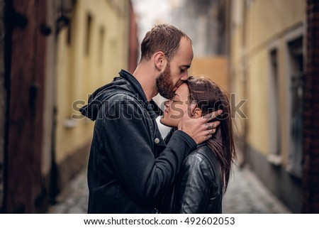 Positive bearded male kissing cute brunette female on a street in an old town.