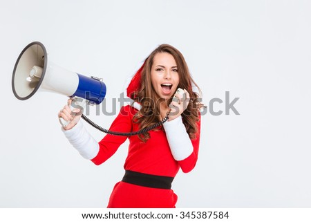 Positive beautiful curly girl in red santa claus costume with hood talking in megaphone isolated over white background