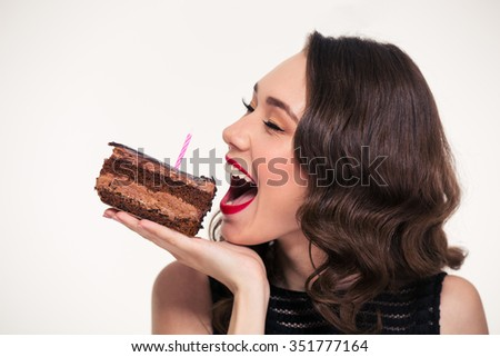 Positive beautiful young woman in retro style biting piece of chocolate birthday cake with candle over white background - stock photo