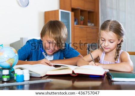 Positive big brother helping little girl to do homework at home
