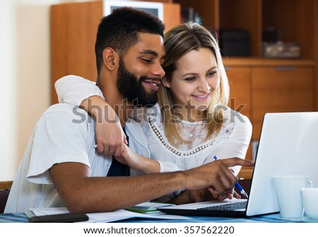 Positive blond girl and black husband shopping online at home - stock photo