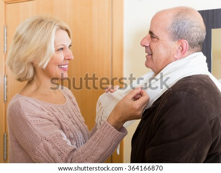 Positive blond wife seeing husband pensioner off at work on the doorstep