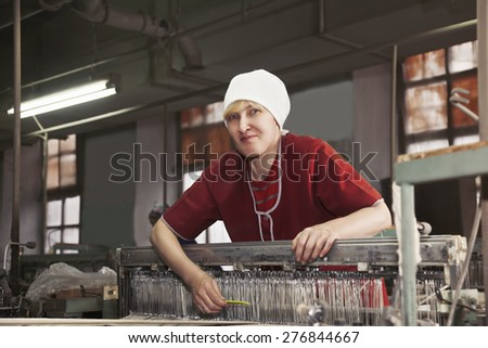 Positive blonde caucasian woman in red smock standing at the factory workshop with yellow comb