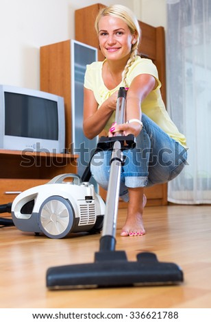 Positive blonde girl hoovering in living room and smiling - stock photo