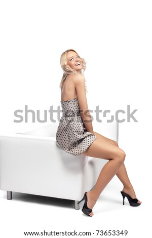 Positive blonde woman sitting on a white leather couch. - stock photo