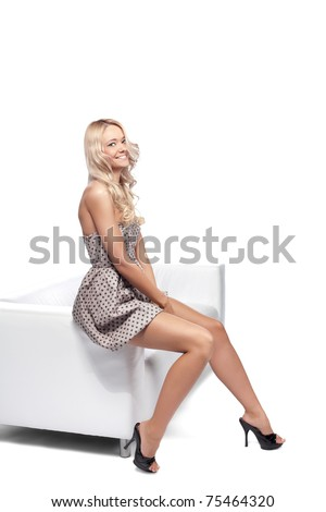 Positive blonde woman sitting on a white leather couch.