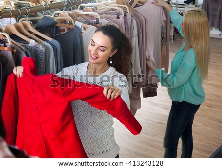 Positive brunette chooses coats in a clothing store - stock photo