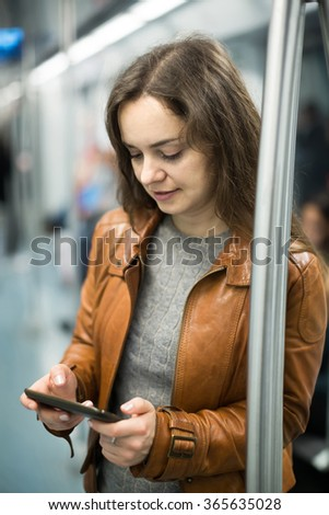 positive brunette girl using cell phone and smiling at subway