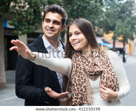 Positive brunette showing direction to Indian guy at the street - stock photo