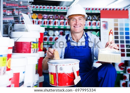positive builder workman in uniform picking paint tin in 
