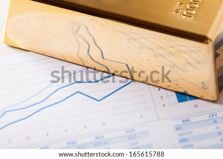 Positive business graphs reflecting in a gold bar - stock photo