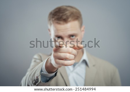 Positive businessman pointing at the camera  - stock photo