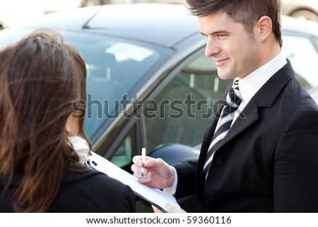 Positive businessman undersign a car contract outdoors - stock photo
